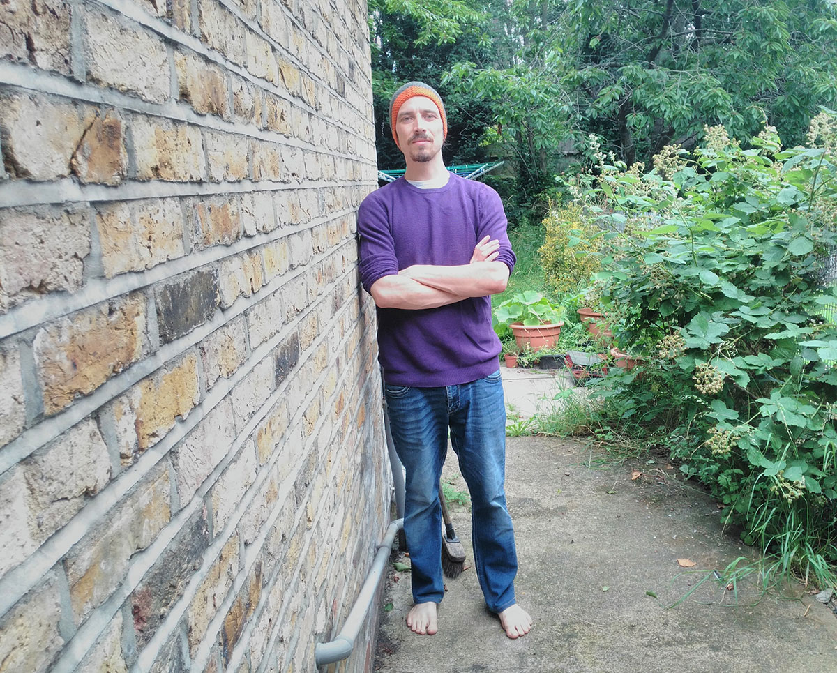 Ben, a man in his thirties, stands leaning against the brick wall of a house looking at the camera with his arms folded. To the side and behind him is the green of a slightly wild garden.