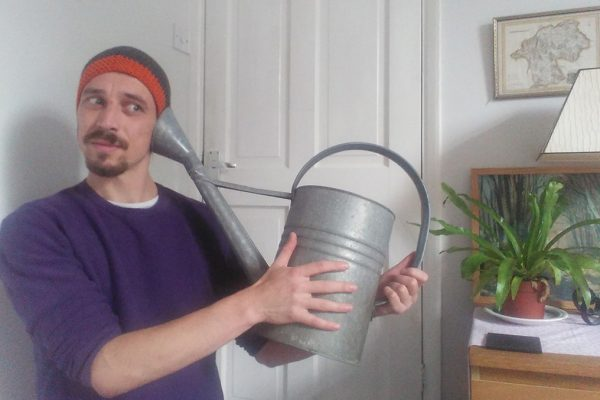 Ben, a man in his thirties, holds a watering can, the spout against his ear, listening. They are in a living room with a plant and a lamp, and he looks amused at whatever he can hear.